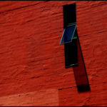 An open window casts shadows against a red wall in Seattle.