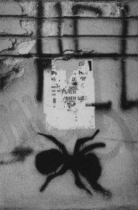 "A black spider is spray painted on a wall underneath a half-ripped poster and spray painted letters ""HEL"""