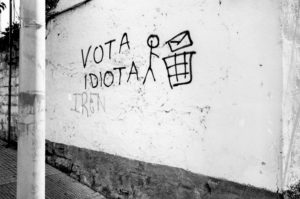 "A white wall with the words ""VOTA IDIOTA"" and a picture of a stick figure throwing a letter in the garbage spray painted on it."