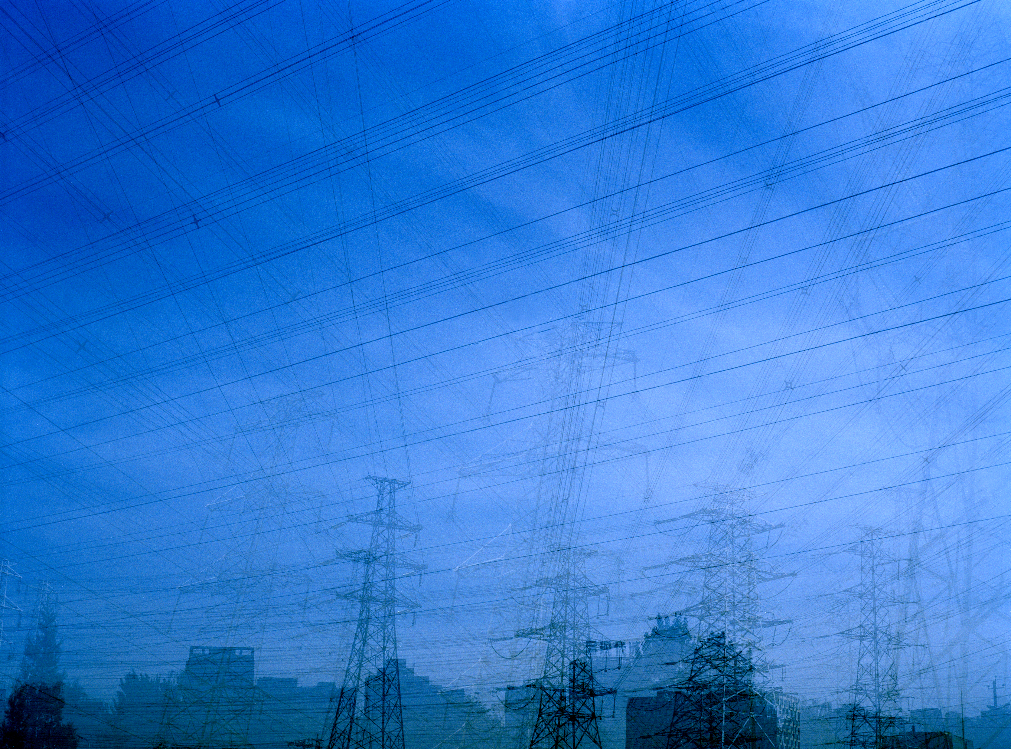 Power Lines and transmission towers can be seen behind a dark, blue sky.