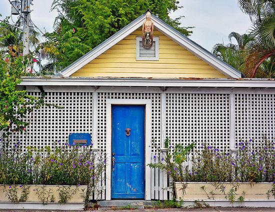 Tropical-like house with a blue door and white and yellow exterior
