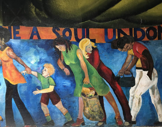 One a soul undone. A mural of people pulling things along like their children, groceries, and lunches.