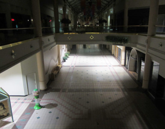 A balcony view of the lower level of a deserted mall, with fluorescent lights illuminating the diner-style tiles and a single gumball machine..