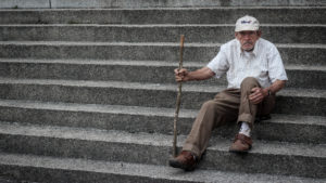 A man is sitting on concrete steps with a baseball hat on and holding a wooden walker stick. He is frowning.