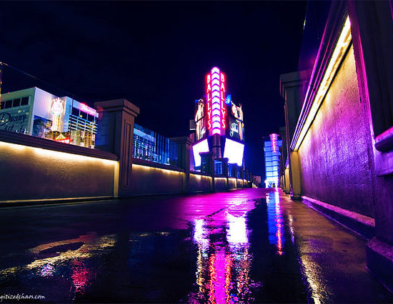 A dark sidewalk in Las Vegas, covered in puddles with a vertical neon sign in the background lighting up the area in colors of violets and blues.