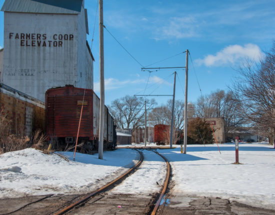 There is a building of metal sheeting and a train car alongside a train track. On the right, there are buildings in the distance, covered mostly by trees. There is snow on the ground.