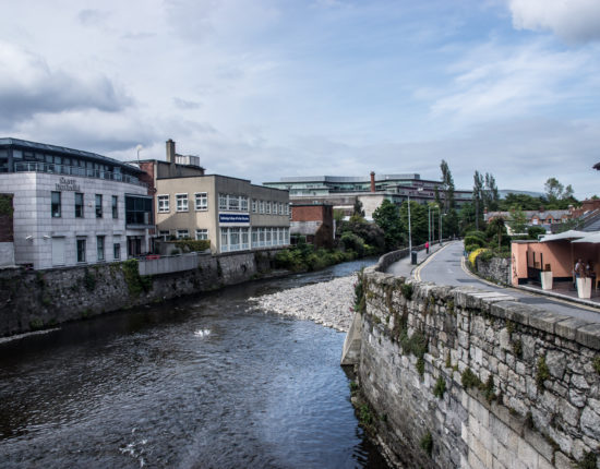 The view from the Ballsbridge Bridge in Dublin, with a curling stone road and business building on either side.
