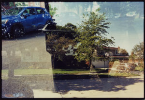 Large black trash can with tree branches sticking out sits adjacent a 3-door blue car is fade with a long one story house with a wide sidewalk in front.