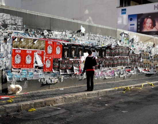 A woman waking a small dog, standing on a sidewalk, and facing a wall covered in posters.