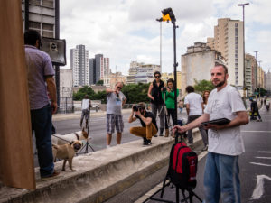 A man holding a backpack while standing in a street while a small group of people take pictures of a man with two medium sized dogs.