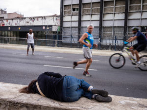 A person laying down on the side of a street while an older man jogs past looking at her, and a person rides a bike. Another man tries to flag down the biker.