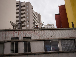 A man smokes on the roof of a building covered with satellite dishes and graffiti, framed by taller buildings in the background.