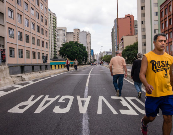 "Two men walking in a street with buildings along the sidewalks. There is a younger man in a yellow shirt walking towards the camera while the older man is walking away with his back turned. The word ""Devagar"" is written in large white words on the street."