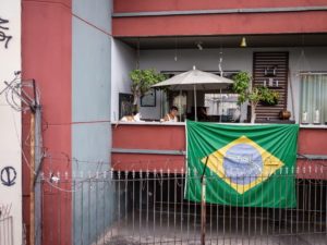 Two people sitting outside underneath a large umbrella on an apartment building with a Brazilian flag hanging off of the patio's ledge.