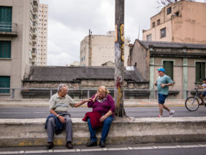 : An elderly man and woman sitting on the side of a street next to a graffitied pole with a man jogging behind them and a row of tan buildings of different heights on the other side of the street.