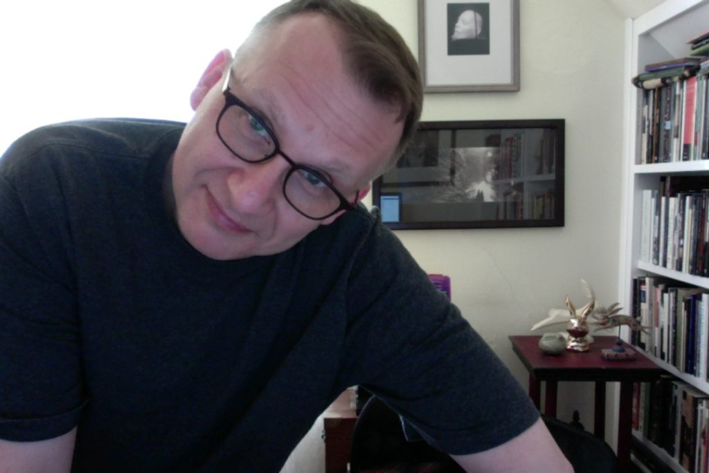Author William Reichard wearing thick-rimmed glasses, smiling at the camera. In the background, there are bookshelves and framed photographs.